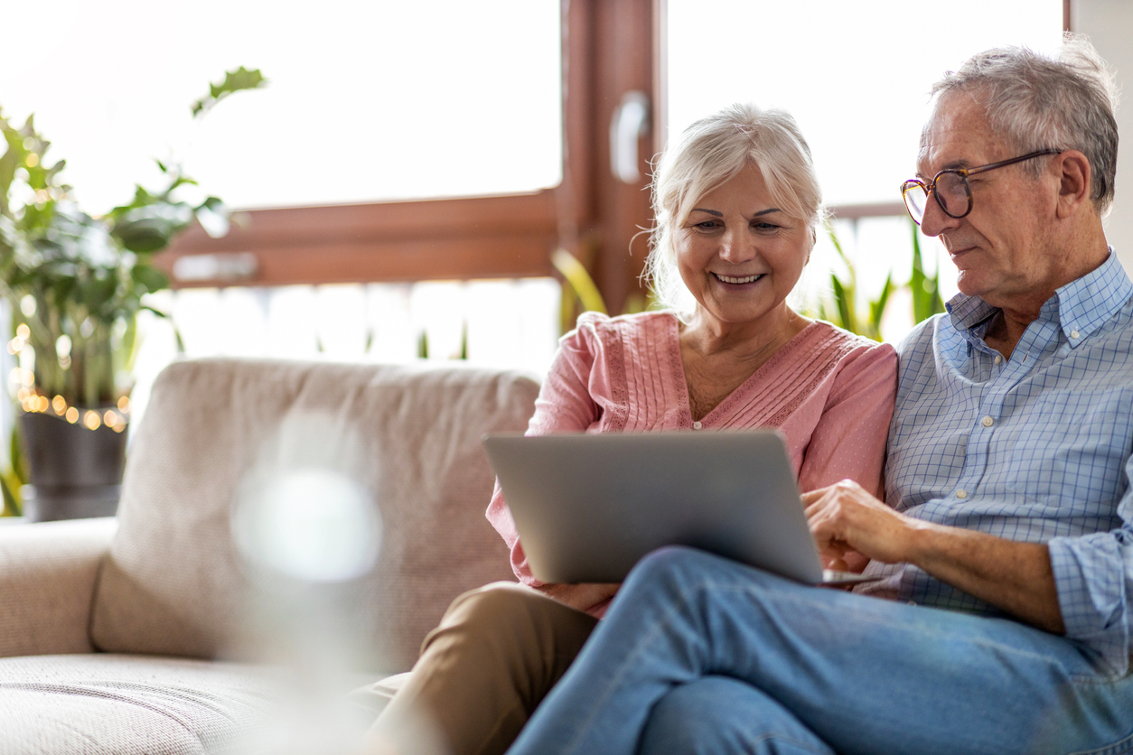 Mature couple using a laptop while relaxing at home, rebuilding trust in insurance